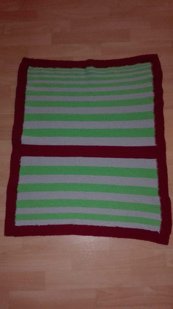 Bild einer grün-grau-gestreifen Babydecke mit roter Umrandung