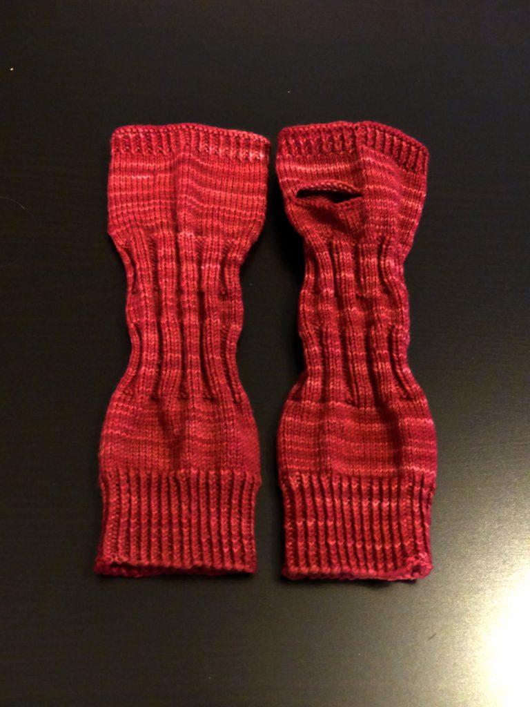"""Auf dem Bild sieht man ein Paar Handstulpen in dunklem Rot. Die Stulpen sind mit 100% Merinowolle gestrickt. Die Färbung heißt """"weinrot""""."""