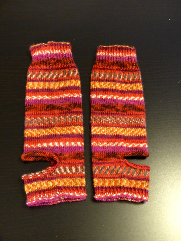 Auf dem Bild sieht man ein Paar Yogasocken. Sie haben statt einer gestricken Ferse ein Loch. Auch am unteren Ende der Socke, wo normalerweise die Sockenspitze ist, sind die Socken offen.