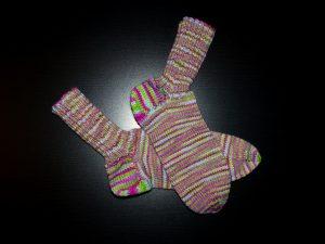 Ein Paar rosa-grün-hellblau geringelte Socken sind von der Seite vor einem dunklen Hintergrund zu sehen.
